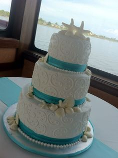 """Jessica"" 3 tier white wedding cake with seashells, swirls, & aqua ribbon border.  Feeds 100.  MSRP $420"