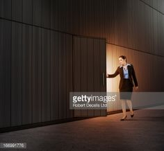 Stock Photo : Woman opening door with light coming from within