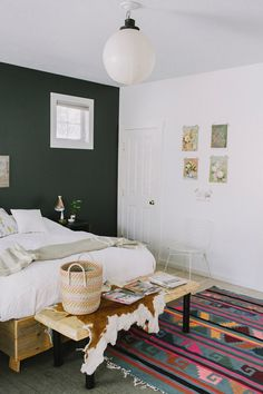 white bed, colorful rug