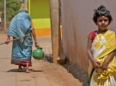 The chore of finding water follows a girl all her life. Will the girl be carrying water like this when she's the same age as the woman? Does the woman carry a burden her granddaughter will never have to bear? Or will the girl only have faint memories of not having easy access to water?