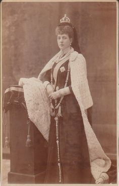 Queen Alexandra of England in mourning for Queen Victoria.  She is wearing Victoria's small crown, a huge multi strand pearl necklace with tassels and down the front of the skirt, three diamond chains suspended by bow brooches.  Picture is heavily retouched; Alexandra is about 58 here.