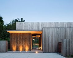 designer house with vertical wood siding and gray, concrete paving and outdoor LED luminaire