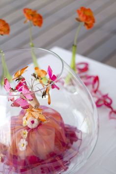 Table centerpiece with orange and pink butterflies on a dummy in a clear round vase. Orange and Pink. Photo Credit : A. Mordant - Click to read more on the Blog: http://www.wedotahiti.com/2-minute-eco-friendly-home-decor/ #tahitiweddingplanner #tahitiweddingpackage
