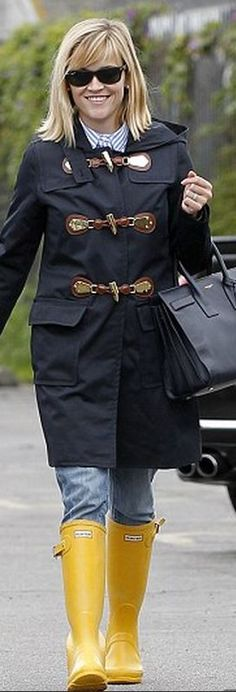 Who made  Reese Witherspoon's black sunglasses, blue toggle rain coat, black tote handbag, and yellow rain boots?