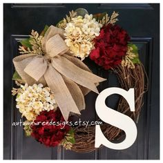 Cranberry red and cream hydrangeas blend together beautifully with cream heather and a double burlap bow... perfect wreath for any time of the year! Pictured with a classic style monogram in cream, choose the initial monogram you would like to make it personal. The grapevine wreath is 18 in diameter. Flowers, bow, and monogram make it approximately 20 in diameter. Each flower, letter and bow is wired and glued to the wreath for optimum durability! SEE ALL my Fall/Winter floral wreaths at ...