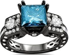 Black Gold Princess Cut Blue and White Diamond Engagement Ring - A very interesting design on this piece gives it a look that's out of this world with this intriguing 18k Black Gold Princess Cut Blue and White Diamond Engagement Ring plated in Rhodium placed within a Prongs, Channel and Bezel setting featuring a large Blue Princess cut center stone along with two White Baguette and Round cut accent sides stones along the custom style shank. The Black Gold Princess Cut Blue and White Diamond…