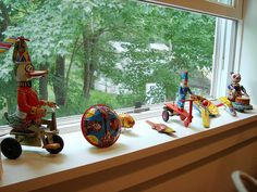 Tin toy collection displayed on a windowsill (part of a larger collection) by mayalu, via Flickr.