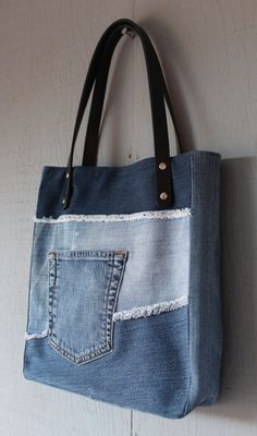 This is a handmade denim upcycled tote bag lined with a Paris inspired cotton with two interior pockets. This tote has two leather straps with two rivets on each side for secure handles. Additional pocket removed from jeans and sewn onto front, great for phone, keys, etc.  Dimensions: 11 (W) x 121/4 (H) x 2 1/2 (D) The straps are 22 Long with a 6 1/2 drop  Please feel free to contact me for custom orders.  Thank you.