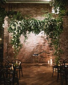 greenery ceremony arch with a rustic brick wall backdrop.