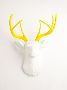 Weird, I know....I just kinda like it.  Faux Taxidermy - The Baron - White W/ Yellow Antlers Resin Deer Head- Stag Resin White Faux Taxidermy. $119.99, via Etsy.