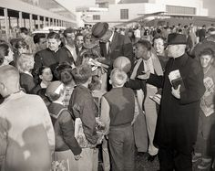 Bill Russell signs autographs for fans at San Francisco International Airport in 1955 after his University of San Francisco team won the NCAA championship