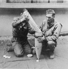 Medical personnel load pre-packed medical supplies into the head of a 155mm round that was to be fired to isolated American troops when poor weather conditions made airdrops impossible. October, 1944.