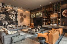 A iluminação na decoração da sala de estar com sofá cinza com almofadas, tapete, mesa de centro com vasos, flores e adornos, plantas, esculturas e obras de arte.