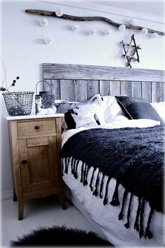Weathered wood headboard, driftwood as wall art. Wood nightstand with white top.