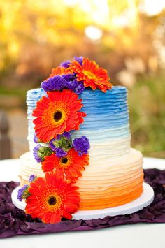 Hello color! How fun is this two-tier wedding cake decorated with blue and orange ombre buttercream and fresh gerber daisies? {Amber Fallon Photo}