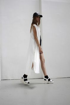 White maxi vest, black hat, white sandals over socks