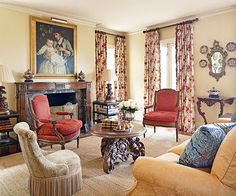 International Style - French, Italian, English, and American styles converge in this living room. The traditional seating area faces a fruitwood mantel that was rescued from a layer of white paint. A slipcovered sofa and a pair of red-upholstered Louis XVI-style bergere chairs gather around a table with rich carving details.