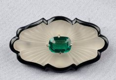 Art Deco, Onyx, Rock Crystal, and Green Tourmaline Brooch, centering a cushion-shape tourmaline measuring approx. 9.50 x 7.20 mm, the carved rock crystal body with shaped onyx back, 14kt gold and platinum mount, lg. 1 7/8 in