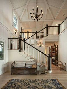 Staircase with dark stained posts and rails, spindles are white, treads are same wood as flooring.
