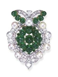 AN ART DECO EMERALD, PEARL AND DIAMOND CLIP BROOCH, BY CARTIER The openwork cabochon emerald cluster, within a single, old European and rose-cut diamond frame, to the pearl trim, measuring approximately 7.70 mm, each surmounted by a single-cut diamond, alternately-set by old European-cut diamonds, further enhanced by single, pear and old European-cut diamond, cabochon emerald and cultured pearl bow and trefoil motifs, mounted in platinum and gold, circa 1934