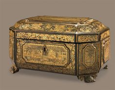 A CHINESE EXPORT BLACK, GILT AND POLYCHROME LACQUER TEA CADDY  CIRCA 1830  Casket form, with raised figural cartouches, with two pewter caddies  6 in. (15 cm.) high, 11 in. (28 cm.) wide, 8 in. (20 cm.) deep