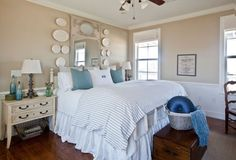 """""""I love the look of a big mirror behind the bed as the headboard, but I couldn't find one wide enough for our king-sized bed to make it look right,"""" Joyce says. """" I love antique ironstone plates and am always looking for an excuse to use them somewhere anyway, so I hung them on either side of the mirror to extend the feel of it."""