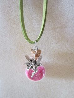 "This super cute Fairy Necklace features Fairy Dust inside of a Miniature Glass Bottle, with a Fairy charm hand strung on a light green Suede leather cord necklace.  The mini bottle is filled with a sparkly pink fairy dust (Glitter) Perfect for anyone who is looking for Fairy Jewelry or a Fairy gift.    This necklace is handcrafted and originally designed by The Charmed Crystal L.L.C.   The necklace measures 20"" inches     Pendant measures 1 1/2"" inches long."