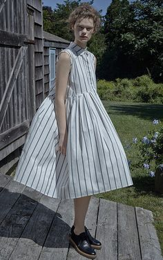 This sleeveless oversized pleated **Brock Collection** dress is rendered in blue and white stripe cotton and features a standard collar, raw finishing detail at the armholes, diagonal seam detail at the sides, and side seam pockets.