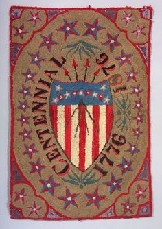 "Wool Centennial Hooked Rug, America, c. 1876, rectangular rug centered with an American shield with stars and arrows flanked by lettering ""C..."