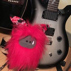 A rockin' red Fuzzling, ready to play the guitar!  This monster is ready for adoption (guitar not included).
