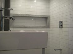 Basement bathroom, tiled in stacked ceramic and marble niche frame. Installed by Mario