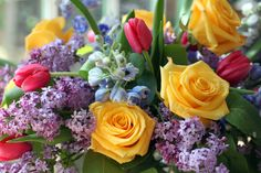 yellow roses lilac delphinium red tulips spring flower arrangement