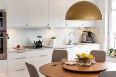 Köksinredning från Ballingslöv med ljusa fina bänkskivor av marmor, ljusa köksluckor och snygg ljus Carraramarmor som stänkskydd vid spis- /disk och arbetsbänk.