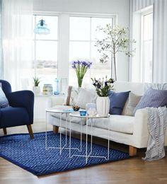 salon alfombra butaca azul dos mesitas flores moderno frescas