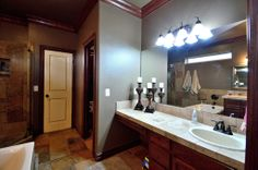 """The """"spa-like"""" master bath has tumbled tile counter tops with oil-bronzed fixtures on separate vanities. """"Her"""" vanity includes an extended make-up area! There is also a large walk-in closet."""