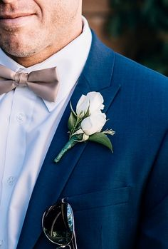 An elegant white double-rose boutonniere with fresh greenery accents for Mike at his later summer Audubon wedding - by Buttercup: AGP Collective.