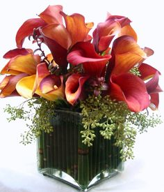 This is a cube vase floral arrangement that features mango calla lilies with accents of seeded eucalyptus.  See our entire selection at www.starflor.com.  To purchase any of our floral selections, as gifts or décor, please call us at 800.520.8999 or visit our e-commerce portal at www.Starbrightnyc.com. This composition of flowers is generally available for same day delivery in New York City (NYC). SQ111
