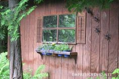 Mirrored window on side of shed - gallery of garden ideas.  If a shed doesn't have a window, create one with an old window frame and/or some mirrors. Here they've added shutters and a flower pot window box.