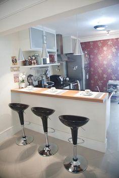 O balcão e o papel de parede ao fundo são elementos que trazem sofisticação a cozinha integrada a sala.