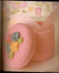 Pink crocheted basket with flowers.