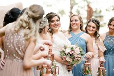 Bridesmaids in mismatched dresses with lanterns as bouquet alternatives