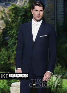 """<p style=""""text-align: left;"""">In recent years, one of the most emergent trends in men's formal wear has been the popularity of dark blue tuxedos and suits. To answer that growing need, Ike Behar Evening has developed some beautiful navy formal options!</p> <p style=""""text-align: left;"""">The Navy 'Blake' Tuxedo is a classy, attention grabbing navy formal favorite! Featuring a single button front, black satin peak lapels, black sat..."""