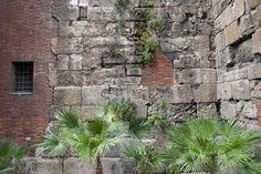 Las murallas de Barcino,Las murallas romanas de Barcelona, de 9 metros de altura, que pueden verse hoy, fueron las segundas que se construyeron en Barcino, después de que las primeras fueran sorteadas por un ataque bábaro en el siglo II d.C. En diferentes puntos del Barrio Gótico se localizan claramente sus restos que se acoplan a edificos posteriores, con el Portal del Bisbe, o del Obispo, en la plaça Nova, como el punto más célebre de las mismas por ser el único portal