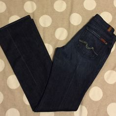 """7 for all Mankind crystal bootcut jeans 28 You're looking at a gently used pair of 7 for all Mankind jeans in size 28.  They are a beautiful, flattering dark blue wash in bootcut style.  The back pockets are accented with Swarovski crystals and silver toned studs. Back left pocket is missing one crystal, but it's barely noticeable unless you examine the jeans closely. Rise measures 8"""", inseam 35"""". Beautiful, like new pair of denim. offers bundles for discounts PayPal trades 7 for all Mankind…"""