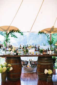 rustic wedding table ideas-The wine casks and a rustic plank makes for an easy outdoor bar setup