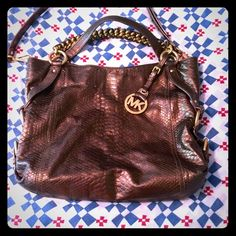 Michael Kors bag, leather, Large This is a beautiful brown to copper colored bag. Made of genuine leather, it has gorgeous gold hardware. It is large and roomy with lots of spaces and compartments to use for storage. This was an everyday bag for me. Signs of wear are normal from use. Leather is somewhat faded at corners. This does not detract from the bag at all. Shoulder strap is detachable, and thus bag is killer gorgeous! MICHAEL Michael Kors Bags