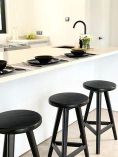 Modern kitchen area with black tap, modern painting, white kitchen bench, black plates