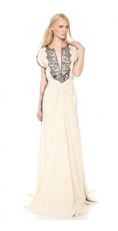 LELA ROSE - FLUTTER SLEEVE GOWN -  $885.25  Dark lace casts elegant contrast against this silk Lela Rose gown, putting a gothic twist on the romantic silhouette. A flattering empire seam accentuates the nipped waist, and artful shutter pleats send easy volume through the trailing, floor-length skirt. Split-V neckline and charming cap sleeves. Silk buttons fasten over the hidden side zip. Fully lined in silk charmeuse.