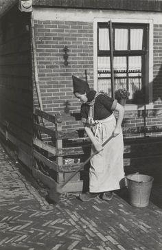 Jonge vrouw uit Volendam, gekleed in daagse dracht. Ze draagt een jak, 'werkbontje' (werkschort), dasje en klompen. 1946 #NoordHolland #Volendam