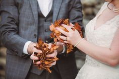 Stunning bride and groom throwing orange and yellow leaves in Autumn / Fall.